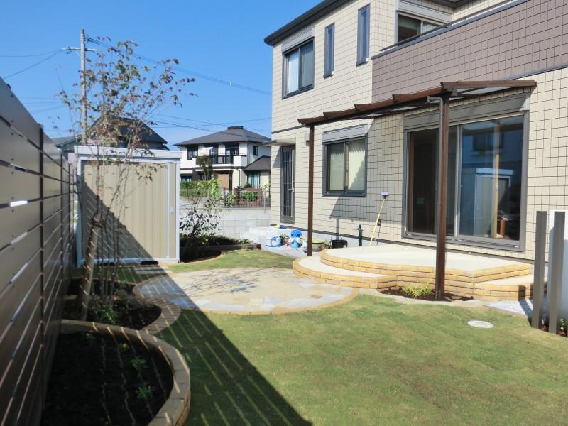 リビングから続く曲線のテラス。物置で庭と畑をゾーン分け。