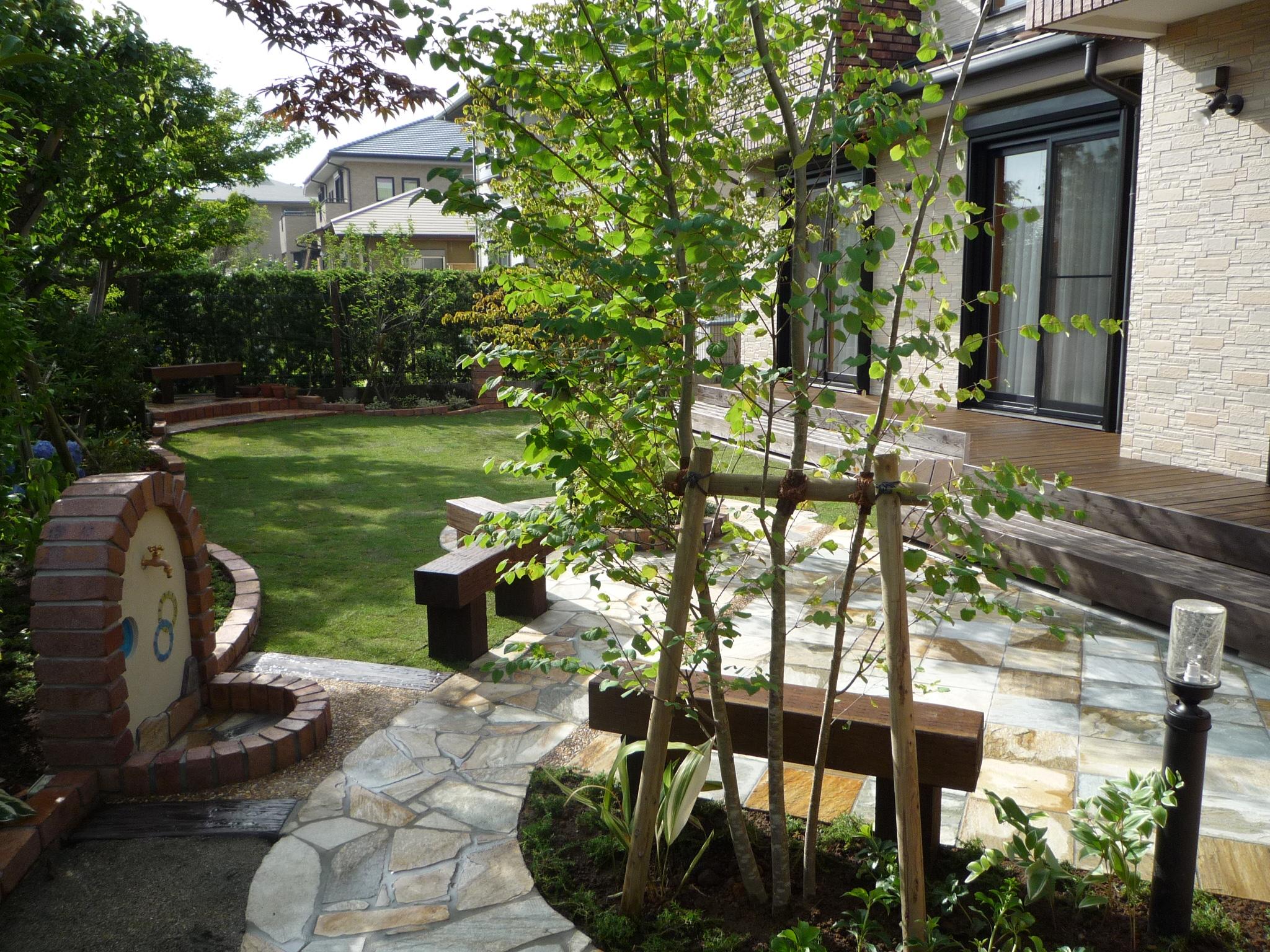 石貼りのテラスに枕木のベンチ、大きな木の木陰が快適空間